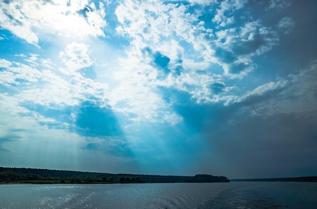 Les rayons de dieu dans le paysage fluvial les rayons du soleil brillent à travers les nuages sur l'eau copy space