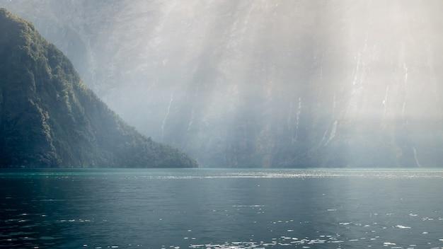 Les rayons du soleil frappant les profondeurs du fjord accentuant la couleur de l'eau verdâtre milford soundnew zealand