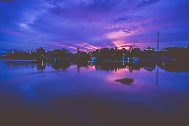 Les rayons du soleil se sont répandus dans le ciel au crépuscule. reflet de l'eau au coucher du soleil. ciel dramatique