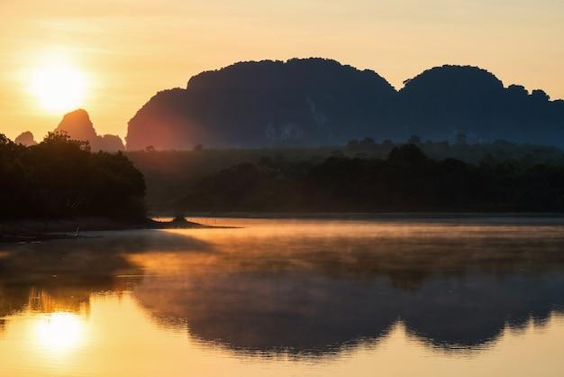 Rayons de lever de soleil avec le magnifique lac nong thale avec brouillard de mouvement et montagnes karstiques le matin à krabi, en thaïlande. destination de voyage célèbre dans le sud de la thaïlande ou du siam.