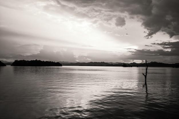 Rayons de lumière du coucher du soleil au paysage du réservoir avec tronc d'arbre au-dessus de l'eau au parc national de khao laem. point de vue pom pee du barrage de vajiralongkorn à kanchanaburi, thaïlande. processus de couleur noir et blanc.