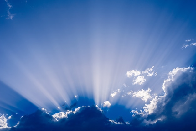 Rayons de soleil s'élevant d'un grand nuage dans un ciel bleu intense un après-midi d'été