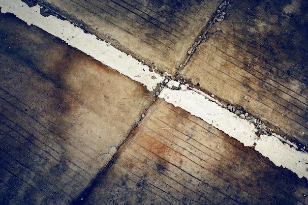 Rayures blanches sur fond de route en béton ancien avec des tons foncés et vignette. fond grunge.