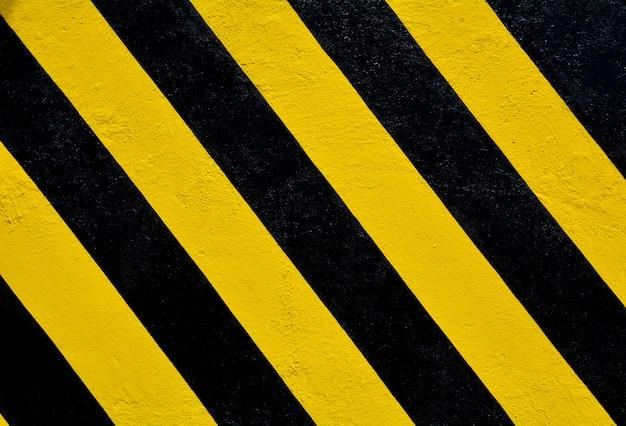 Rayures jaunes et noires sur la surface en béton - fond