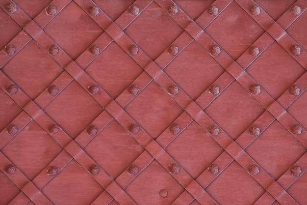Rayures rouges forgées avec rivets en bronze brillant. élément de porte ancienne