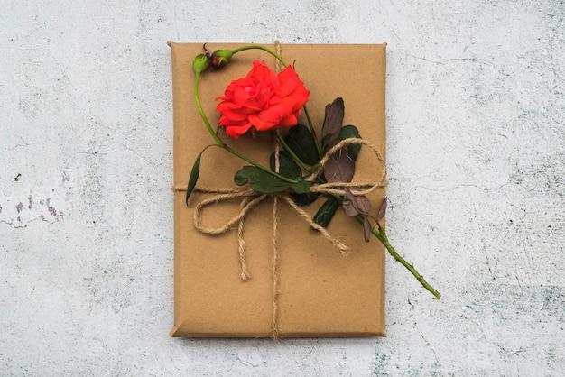 Re rose fleur sur la boîte cadeau enveloppé sur le fond blanc grunge