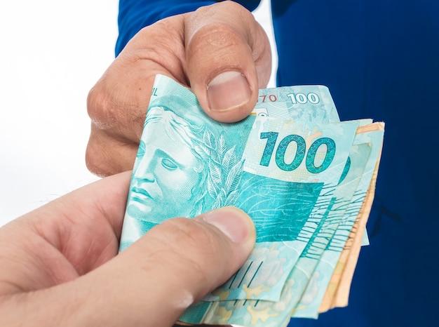 Real brl deux hommes faisant des affaires avec des billets d'argent du brésil sur fond blanc