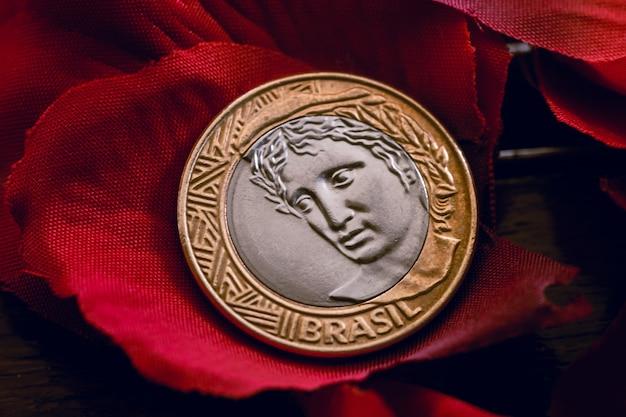 Real brl une pièce de monnaie brésilienne sur des pétales de rose artificiels