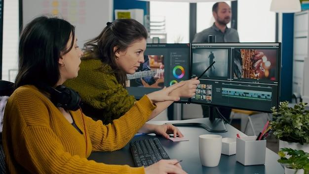 Réalisateur d'art vidéo expliquant à une vidéaste les étapes de la réalisation d'un montage de film pointant sur...