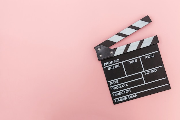 Réalisateur film vide faisant clap ou ardoise de film isolé sur fond rose