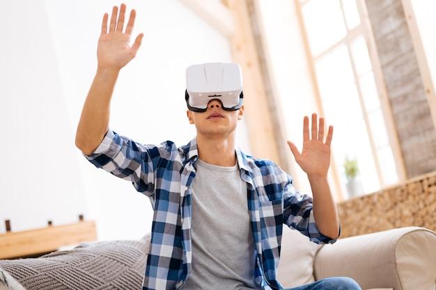 Réalité virtuelle. adolescent élégant et bien construit concentré portant un casque vr et se détendant assis sur le canapé