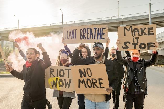 Des rebelles avec des pancartes criant dans la rue et levant les poings tout en manifestant en ville