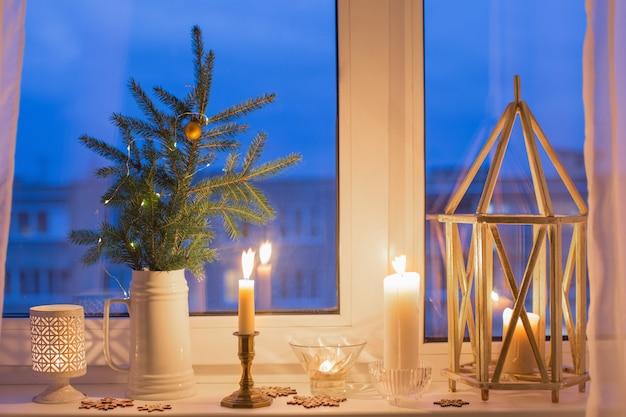 Le rebord de la fenêtre du soir de noël avec des bougies allumées