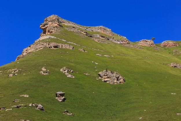 Rebord en pierre d'une crête rocheuse contre le ciel bleu.