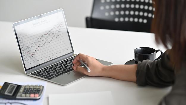 Recadrage de données commerciales femme d'affaires analyste dans un ordinateur portable.