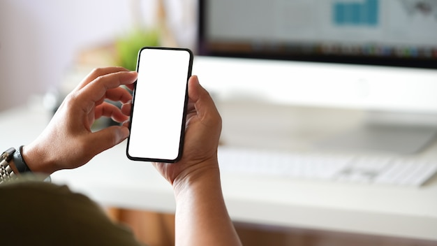 Recadrage de l'homme à l'aide d'un smartphone au bureau