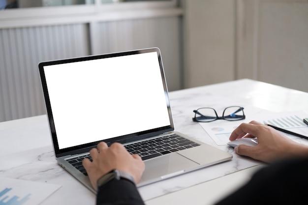 Recadrage des mains à l'aide d'un ordinateur portable. ordinateur portable à écran blanc pour le montage d'affichage graphique.