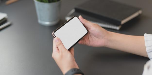 Recadré coup de femme d'affaires professionnel tenant un smartphone écran blanc horizontal