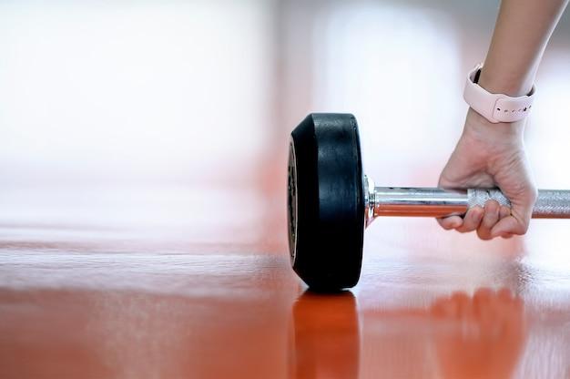 Recadré coup de jeune main féminine soulevant des haltères dans la salle de gym