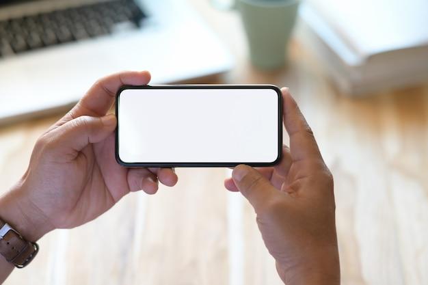 Recadré coup de main de l'homme sur smartphone avec écran blanc isoler vierge