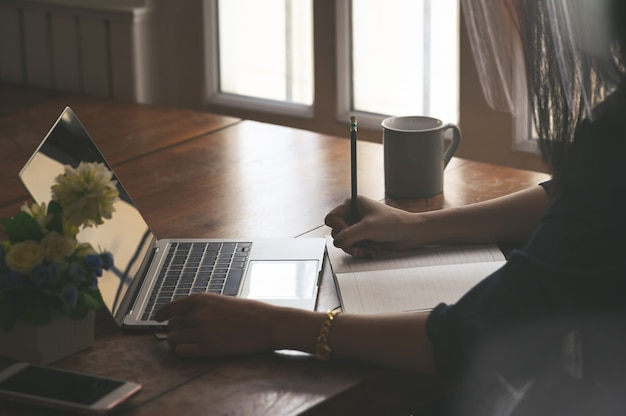 Recadrée coup femelle en utilisant un ordinateur portable et mouillant sur papier.