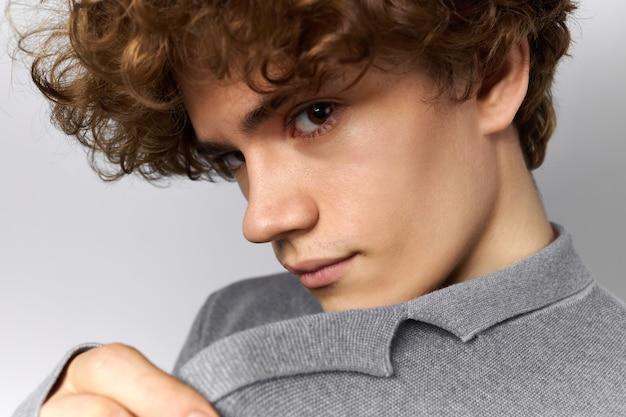 Recadrée en gros plan image de beau jeune homme à la mode avec une coiffure élégante posant sur fond gris tirant le col de sa veste, regardant la caméra.