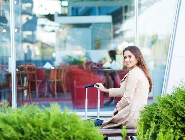 Recadrée image voyageur touristique femme croisée en été vêtements décontractés avec valise sur la route en ville en plein air