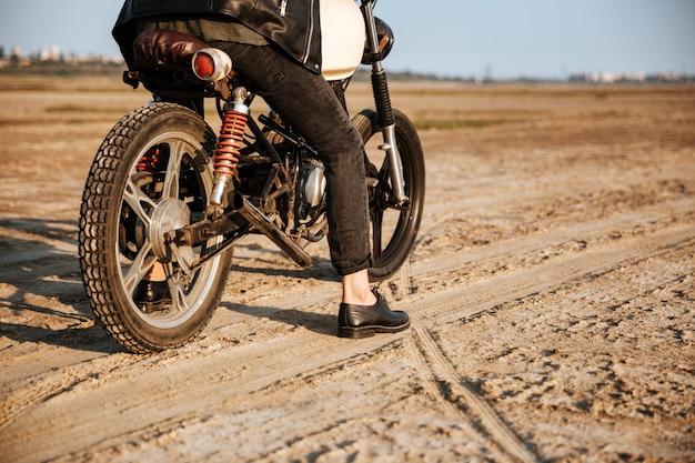 Recadrée d'un jeune homme brutal dans une veste noire et des lunettes conduisant une moto rétro