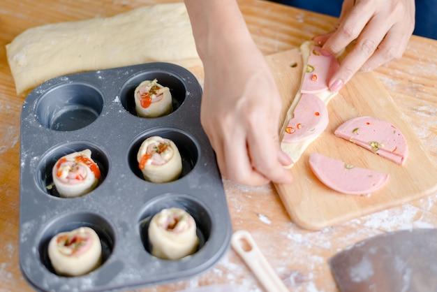 Recadrée main de femme préparant la pâte dans la plaque de cuisson