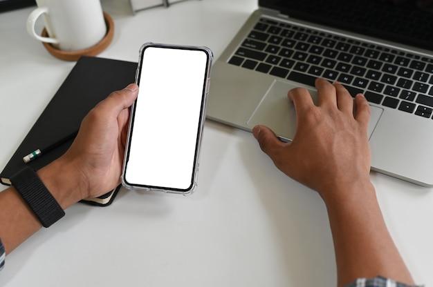 Recadrée des mains à l'aide de maquette smartphone sur le bureau avec un tracé de détourage.