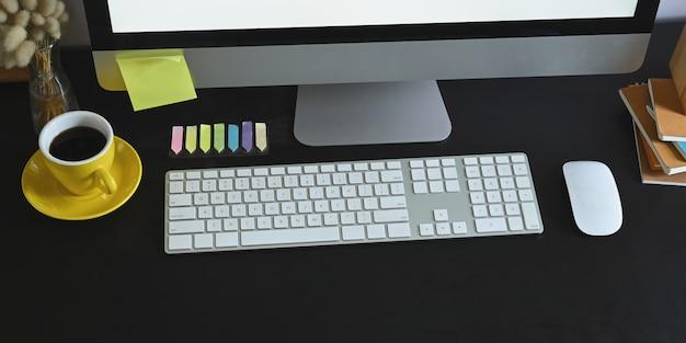 Recadrée de moniteur d'ordinateur mettant sur un bureau de travail noir avec clavier sans fil, souris, pile de livres, tasse de café et affichez-le. concept d'espace de travail ordonné.