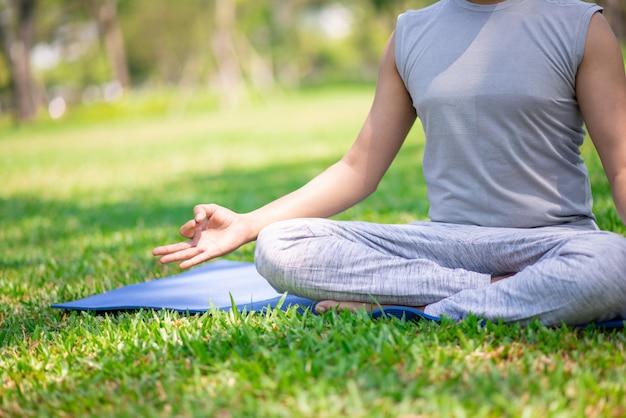 Recadrée portrait d'un homme assis sur l'herbe en posture de lotus.