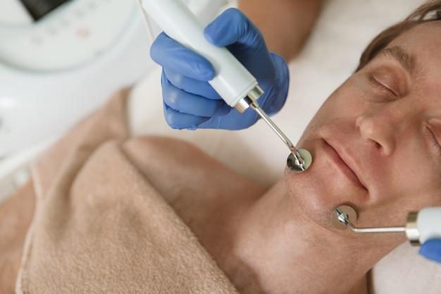 Recadrée de près d'un homme mûr bénéficiant d'un traitement de cosmétologie du visage matériel à la clinique de beauté