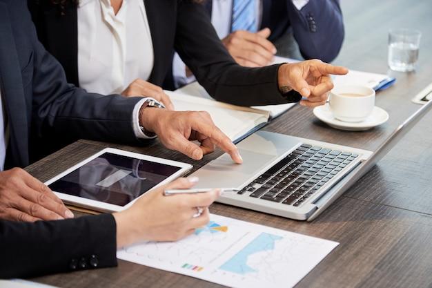 Recadrer des collègues à l'aide d'un ordinateur portable à la table