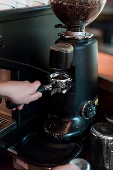 Recadrer les mains broyer le café dans le porte-filtre