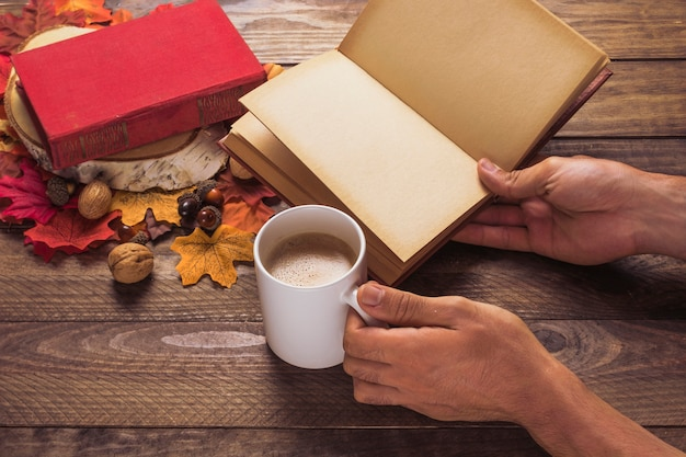 Recadrer les mains avec le livre et le café près des feuilles et des noix