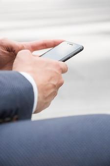 Recadrer les mains en parcourant le smartphone dans la rue