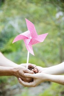 Recadrer les mains avec le sol et le moulin à vent de papier