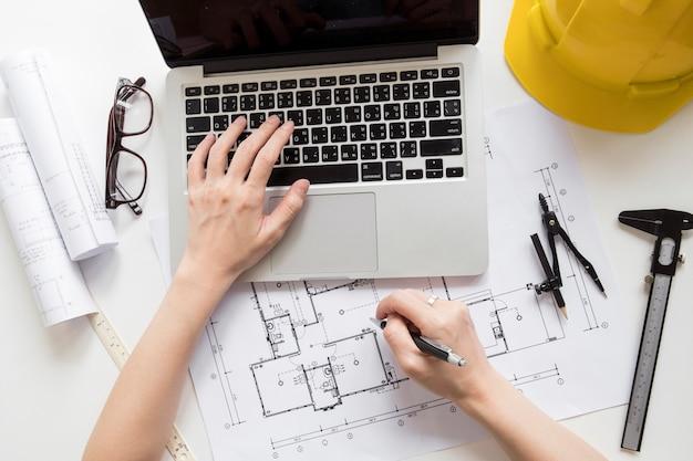 Recadrer les mains en utilisant un ordinateur portable et prendre des notes sur le projet