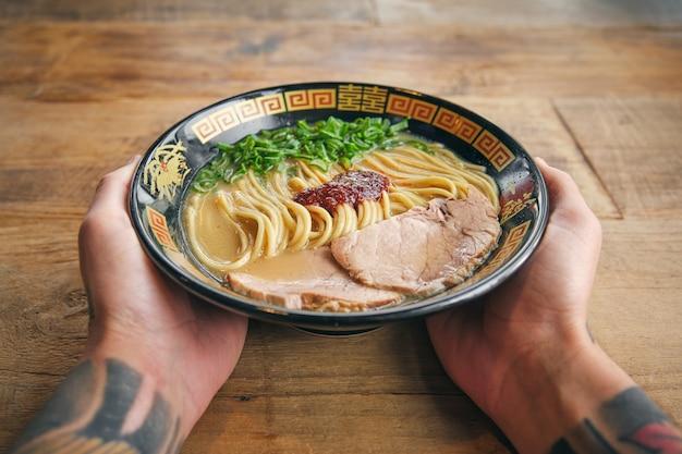 Recadrer une personne tatouée avec un bol de délicieux ramen pour le déjeuner