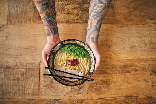 Recadrer une personne tatouée avec de délicieux ramen et des baguettes
