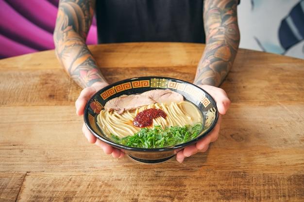 Recadrer une personne tatouée avec de délicieux ramen dans un bol ornemental
