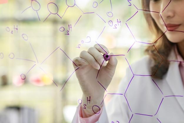 Recadrez une femme scientifique méconnaissable avec un marqueur écrivant des formules chimiques sur une planche de verre tout en travaillant avec des collègues en laboratoire.