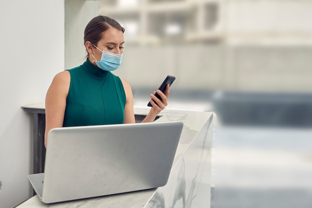 Recepcionista con cubrebocas contestando mensajes en su celular mientras trabaja