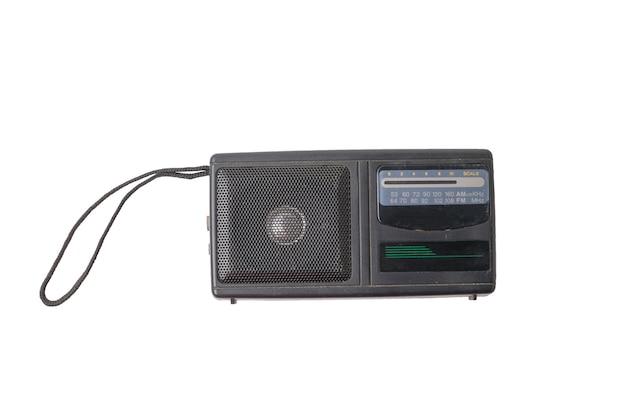 Récepteur radio antique avec une poignée de corde isolée sur fond blanc.