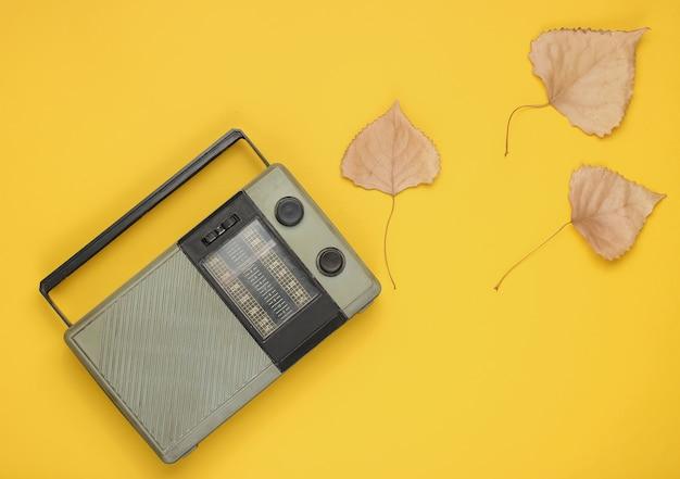 Récepteur radio fm rétro sur fond jaune avec des feuilles d'automne tombées