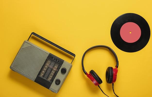Récepteur radio fm de style rétro casque filaire disque vinyle sur fond jaune