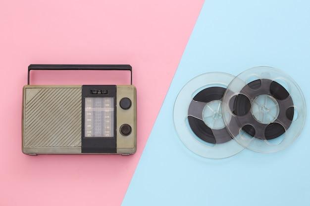 Récepteur radio portable et bobine de bande magnétique audio sur pastel bleu rose