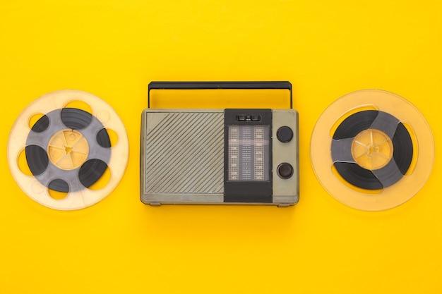 Récepteur radio portable rétro et bobine de bande magnétique audio sur jaune