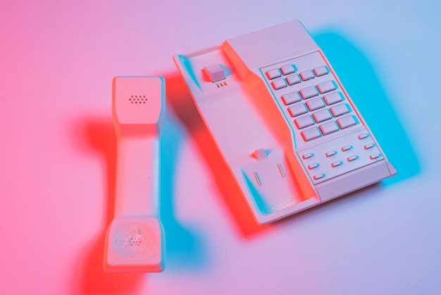 Récepteur et téléphone fixe sur fond rose avec une ombre bleue